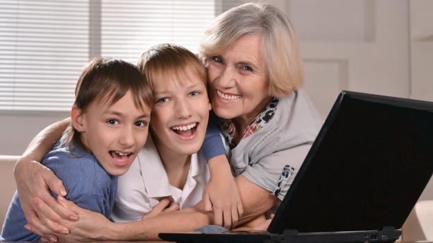 Zwei Jungen mit Gorssmutter vor dem Laptop