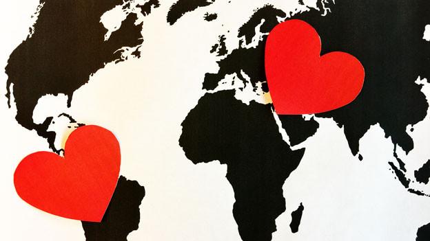 Zwei rote Herzen auf einer Weltkarte.