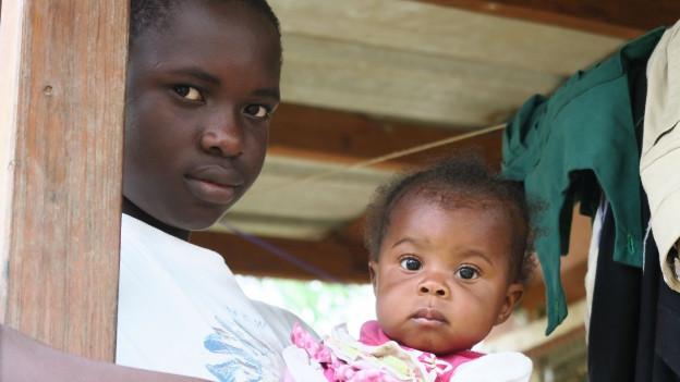Ein kleines Mädchen und seine Mutter nach der Zerstörung durch Hurrikan Matthew.