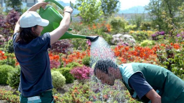 Eine Gärtnerin begiesst ihren Kollegen mit Wasser aus einer Spritzkanne.