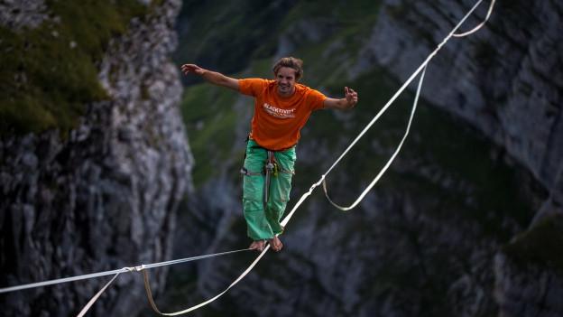 Junger Mann balanciert auf einem Seil in den Schweizer Bergen
