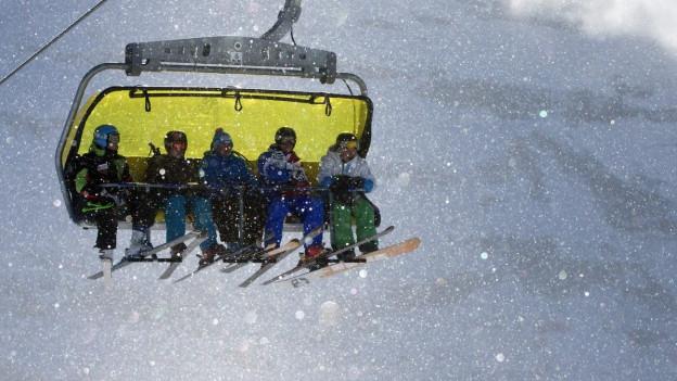 Schneesportler in Bergbahn.