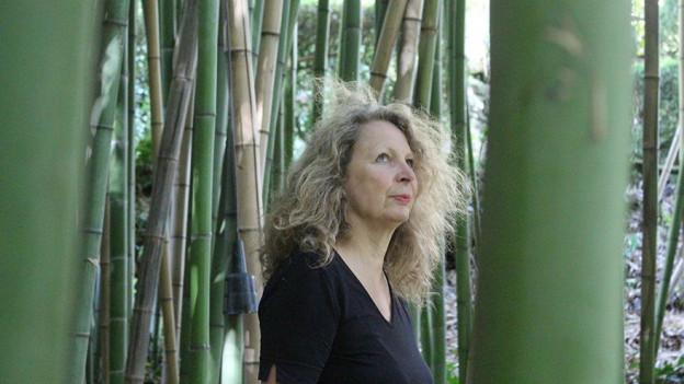 Jacqueline Dolder steht inmitten eines riesigen Bambusheines in ihrem Kunstgarten La Serpara.