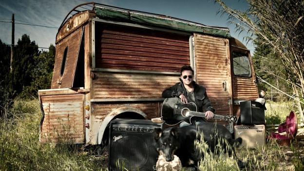 Florian Ast sitzt mit Gitarre vor einem alten Lieferwagen