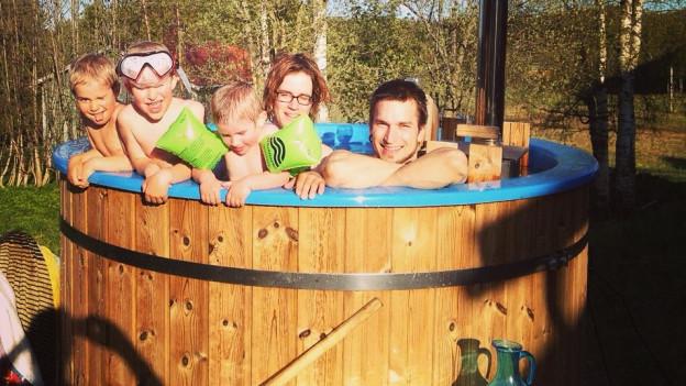 Familie Wetter sind in einem typisch schwedischen Hot Tub unter freiem Himmel. Ein Whirlpool der mit Holz angeheizt wird.