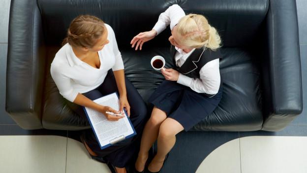 Zwei Arbeitnehmerinnen diskutieren