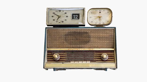 Auf einem alten Radiogerät stehen zwei Wecker.