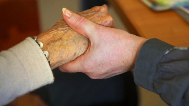 Eine junge Hand hält die Hand eines alten Menschen.