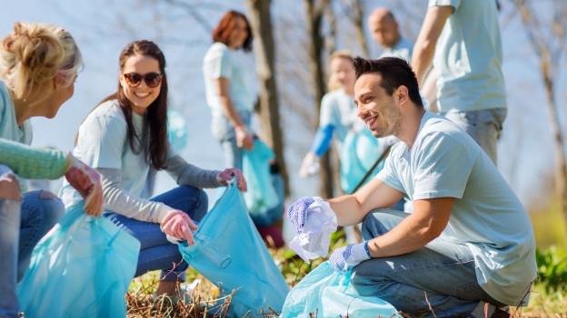 Auf dem Bild sammeln Freiwillige draussen Müll zusammen.