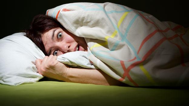 Frau liegt wach im Bett und hat Angst.
