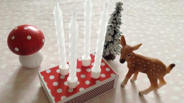 Zündholzschächteli mit vier Kerzchen und daneben Deko
