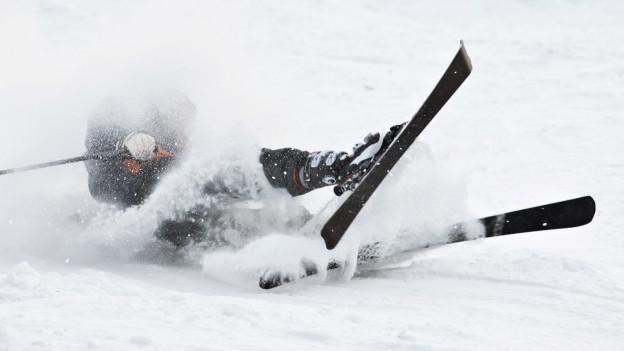 Ein Skifahrer stürzt auf der Piste.