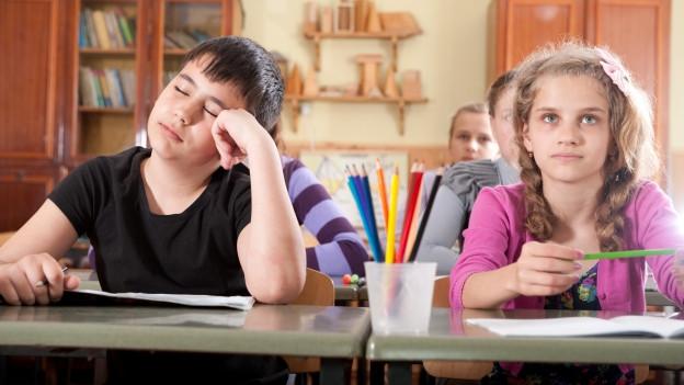 Eine Schulbank, links ein Schüler, der schläft; rechts eine hellwache Schülerin