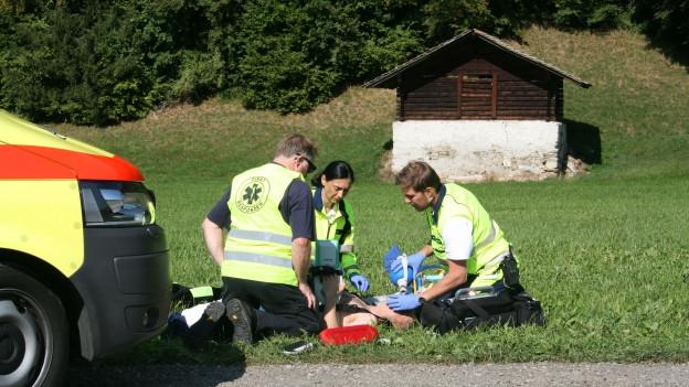 Drei freiwillige Helfer kümmern sich um einen Verunfallten.