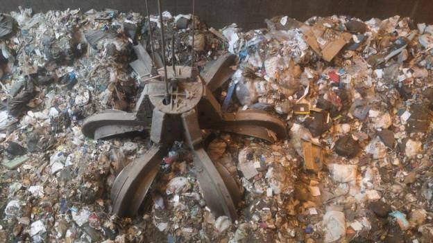 Greifarm holt sich Abfall für Verbrennung.
