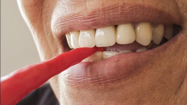 Frau nimmt Chilischote in den Mund.