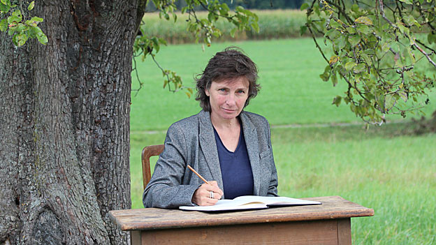 Margrit Konrad sitzt an einem Tisch unter einem Baum.