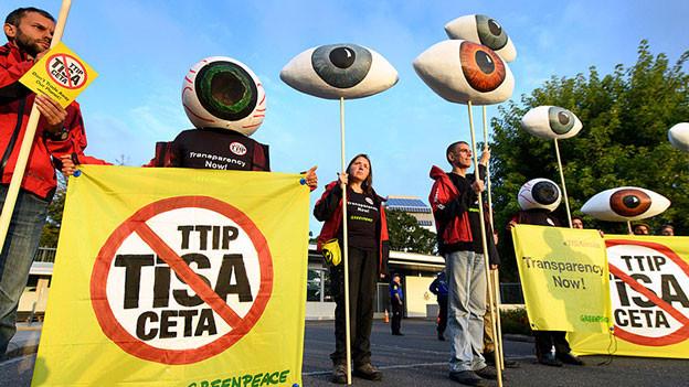 Aktivisten mit Transparenten und gebastelten Augen stehen auf einem Platz.