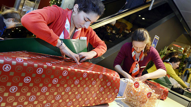 Angestellte packen Weihnachtsgeschenke ein.