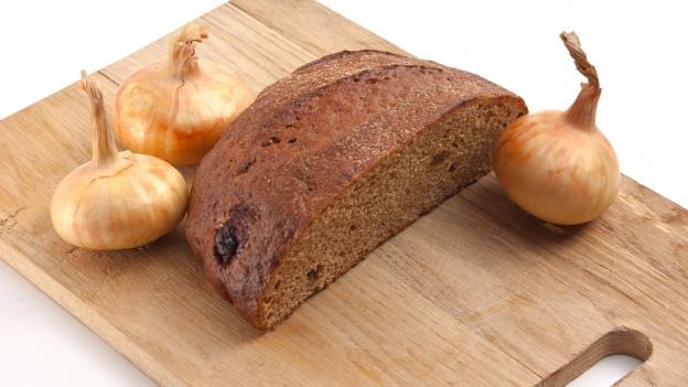 Zwiebeln und Brot auf Schnittbrett.