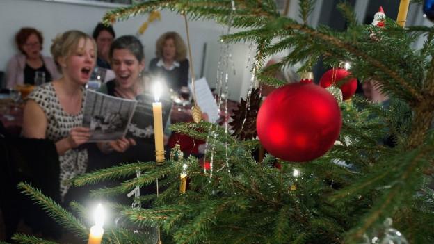 Singende Weihnachtsgesellschaft in einer Stube mit Tannenbaum.