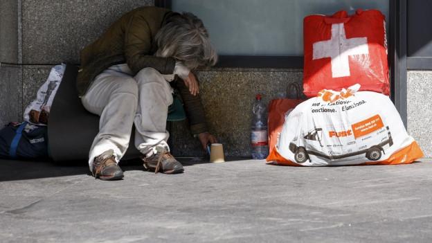Ein Obdachloser sitzt zusammengesunken auf der Strasse.