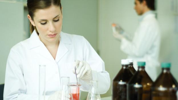 Eine Frau im weissen Kittel, ein Mann im Hintergrund, Laborstimmung