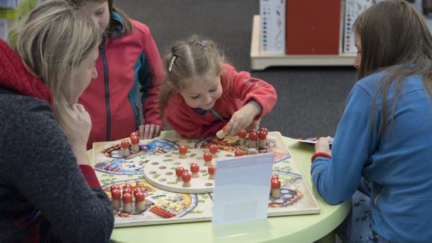Ein Mädchen spielt mit Erwachsenen ein Gesellschaftsspiel.