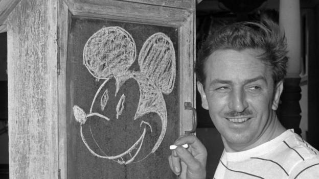 Eine überdachte Wandtafel, darauf mit Kreide der Kopf von Mickey Mouse, rechts davon der junge Walt Disney mit weissem Streifen-T-Shirt und weisser Kreide in der Hand.