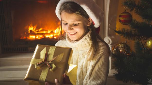 Ein Mädchen in festlichem Pullover und einem Geschenk in einer Stube vor leuchtendem Weihnachtsbaum.