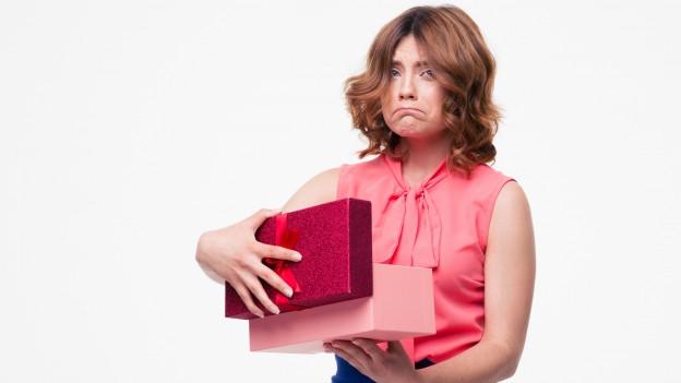 Frau mit entsetztem Blick, weil das Überraschungsgeschenk keine Freude macht