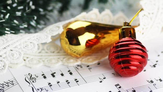 Weihnachtsschmuck liegt auf Musiknoten