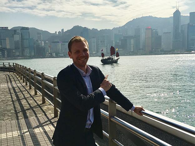 Fabio Weiss steht am Ufer des Perflusses in Hong Kong. Im Hintergrund die Skyline der chinesischen Metropole.