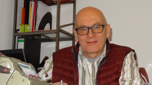 Herbert Kündig sitzt an seinem Schreibtisch aus hellem Holz.