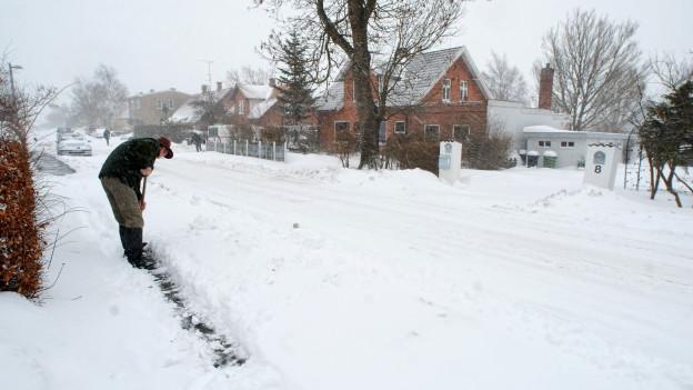 Ein Mann schaufelt Schnee auf der Strasse.