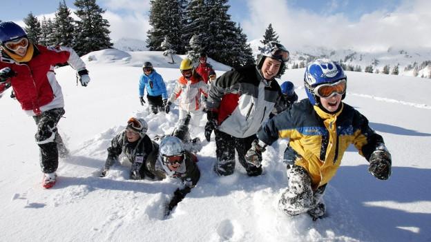 Kinder- und Jugendliche stampfen in einem Skigebiet durch den Tiefschnee und lachen.