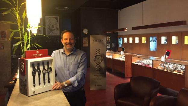 Ueli Bangerter in seinem Uhrengeschäft in Kingston. Neben ihm ein Gestell mit Schweizer Uhren.