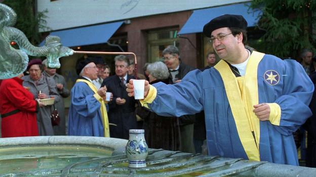Aus einem Brunnen in Basel fliesst Hypokras. Ein Mann füllt seinen Becher.