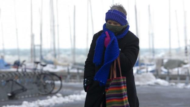 Frau dick eingewickelt trotzt der Kälte.