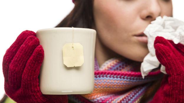 Eine Tasse Tee in der Hand einer kranken Frau.