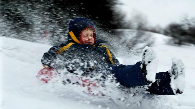 Ein Kind flitzt auf einem Schneebob einen Hang hinunter