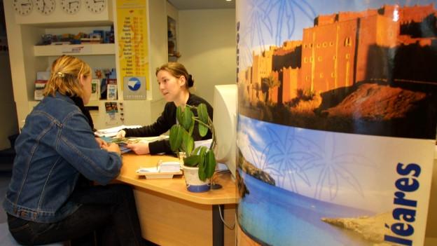 Blick von rechts auf ein Pult, dahinter die Reisebüro-Fachfrau, davor eine Kundin, im Vordergrund eine Werbesäule mit einem Plakat mit dem Aufdruck «Baleares»