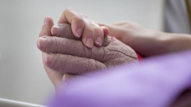Eine gesunde Hand hält im Spital die Hand eines Brandverletzten; jeder Finger ist einzeln in dickem braunen Verband gwickelt