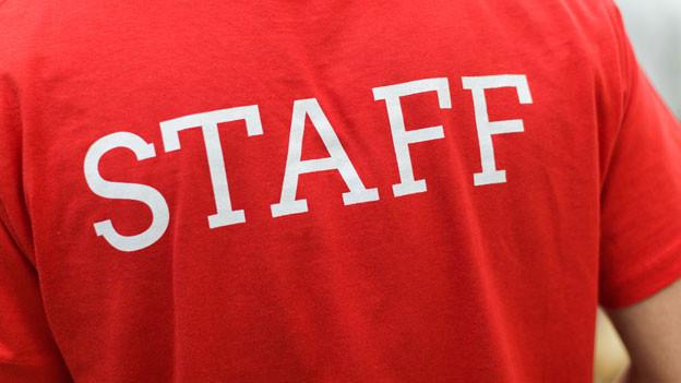 Auf einem roten T-Shirt steht in weisser Schrift «Staff».
