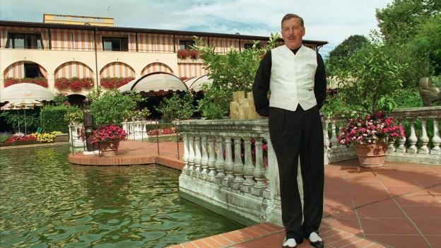 Eine Hotelanlage im Terracotta-Stil, im Vordergrund Hans C. Leu im schwarzweissen Westen-Anzug und Gamaschen-Schuhen