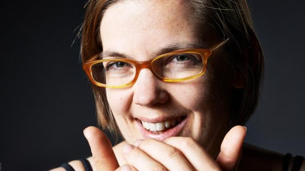 Nahaufnahme von der lacheneden Selina Senti. Sie trägt eine Hornbrille und die Daumen zeigen nach oben.