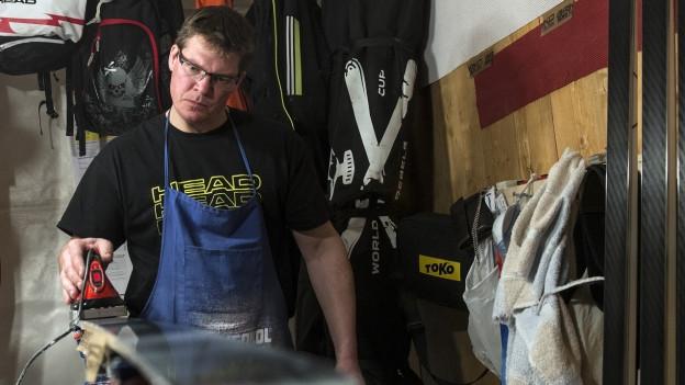 Mann in seiner Skiwerkstatt schleift die Kanten eines Skis.