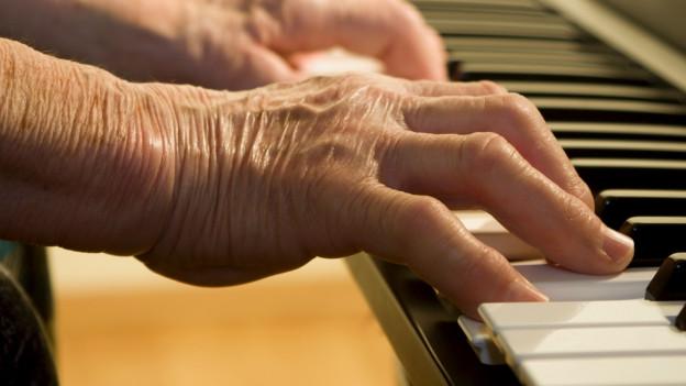 Die Hand eines älteren Menschen spielt auf der Klaviertastatur.