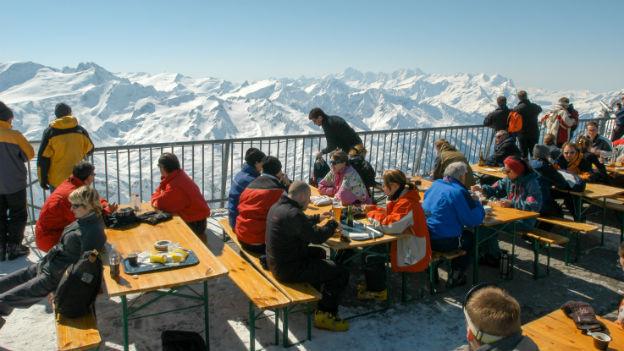 Leute im Pistenrestaurant mit Aussicht auf die Berge.