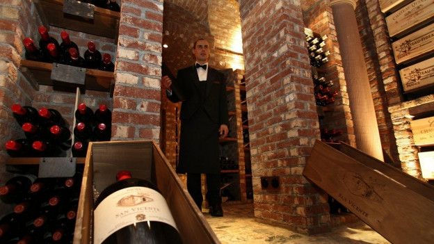 Sommelier steht in einem Weinkeller.